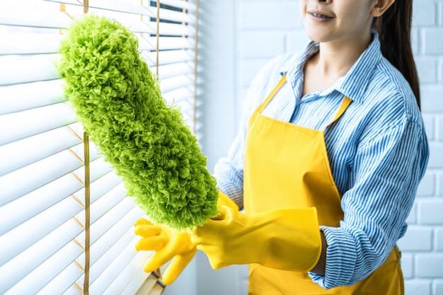 Reinigungs- und reinigungskonzept, glückliche junge frau in den gelben gummihandschuhen, die staub mit federbesen abwischen, während auf fenster zu hause reinigen