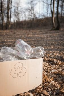 Reinigungsbereich für junge freiwillige in holz, mit plastikflasche im öffentlichen park.