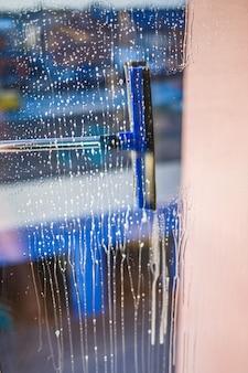 Reinigungsbürste für fenster. großes fenster in einem mehrstöckigen gebäude, reinigungsservice. fensterreinigung in hochhäusern, häuser mit einer bürste. staubentfernung und glasreinigung.