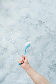 Reinigungskonzept. erhöhte hand, die blauen pinsel hält. speicherplatz kopieren