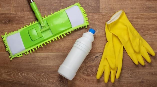 Reinigungsmittel. grüner plastikmopp, handschuhe, flasche waschmittel auf holzboden. desinfektion und reinigung im haus. draufsicht