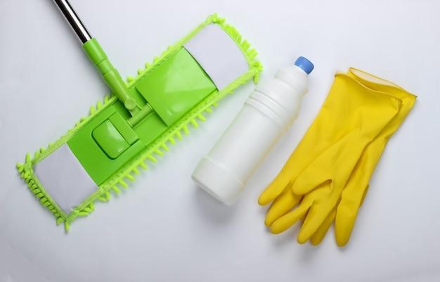Reinigungsmittel. kunststoff grüner mopp, handschuhe, flasche waschmittel auf weißer oberfläche. desinfektion und reinigung im haus. draufsicht