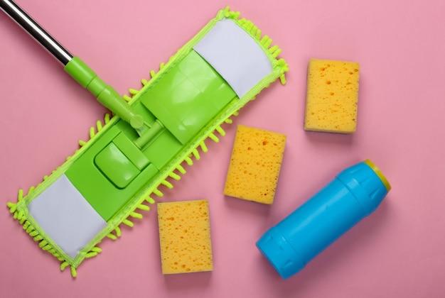 Reinigungsmittel. kunststoff grüner mopp, schwämme, flasche waschmittel auf rosa oberfläche. desinfektion und reinigung im haus. draufsicht