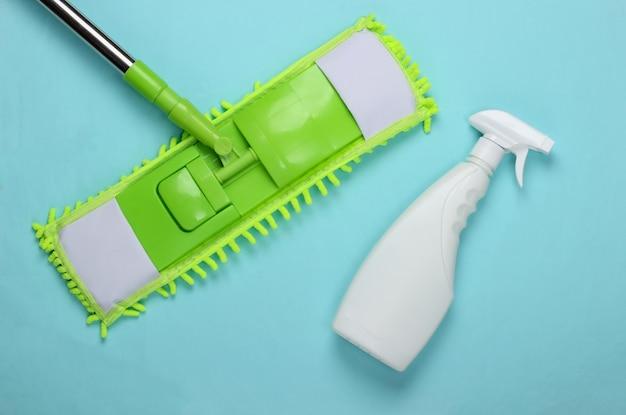 Reinigungsmittel. kunststoff grüner mopp, sprühflasche auf blauer oberfläche. desinfektion und reinigung im haus. draufsicht