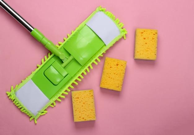Reinigungsmittel. kunststoff grüner mopp und schwämme auf rosa oberfläche. desinfektion und reinigung im haus. draufsicht