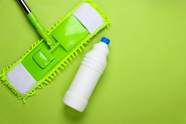 Reinigungsmittel. plastikmop, flasche waschmittel auf grünem hintergrund. desinfektion und reinigung im haus. draufsicht