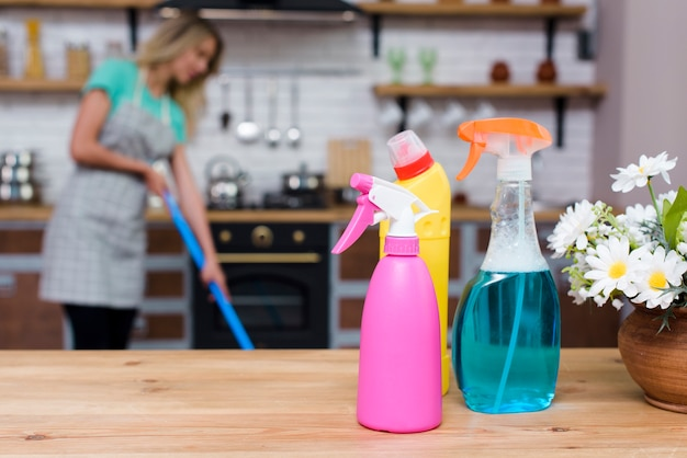 Reinigungsmittel und sprühflaschen auf hölzernem schreibtisch vor der frau, die zu hause wischt