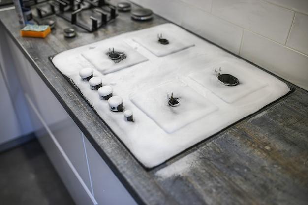 Reinigungsmittelschaum auf einem gasherd reinigung der küche