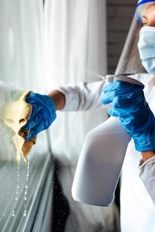 Reinigungspersonal desinfiziert das haus gegen viren und trägt eine transparente schutzmaske