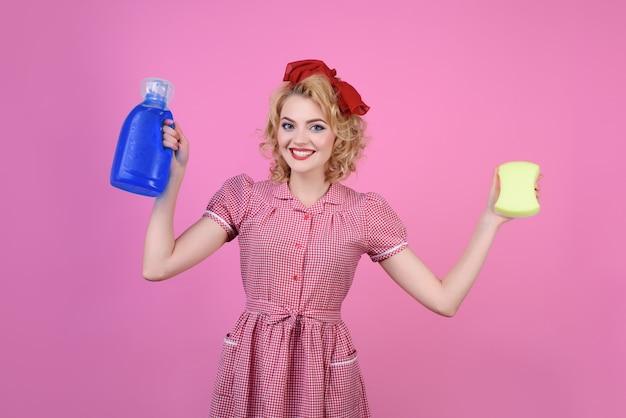 Reinigungsporträt von pin-up-frau mit reinigungsprodukten sinnliche frau mit hellem make-up hält