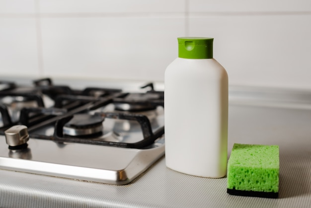 Reinigungsprodukt in plastikflasche am gasherd.