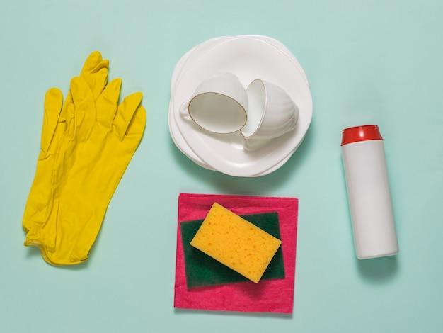 Reinigungsprodukte und sauberes weißes geschirr auf blauer oberfläche