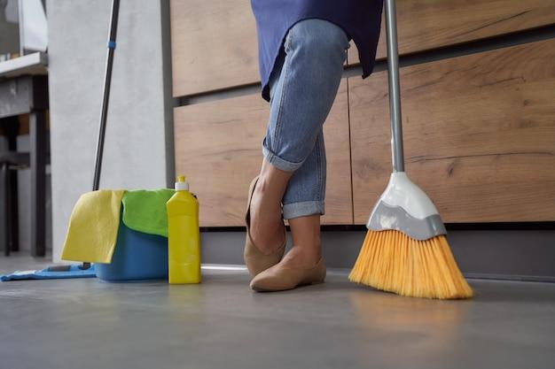 Reinigungsservice. abgeschnittene aufnahme einer frau, die einen besen zum kehren des bodens zu hause hält. mopp und plastikeimer oder korb mit reinigungsprodukten auf holzboden. hausarbeit, reinigung, housekeeping-konzept