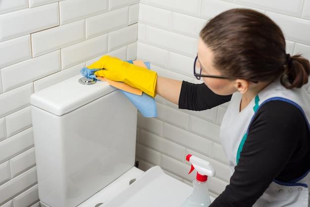 Reinigungsservice. frau die toilette waschen