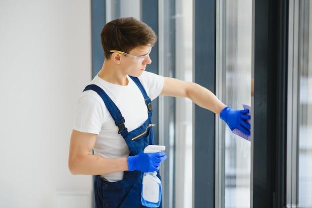 Reinigungsservice kam, um neues haus zu reinigen. fleißiger mann sauber fenster reinigen. seitenansicht