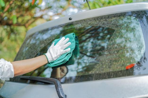 Reinigungsstaub schmutziges hinteres fensterglasauto mit grünem microfiber stoff im feiertag.