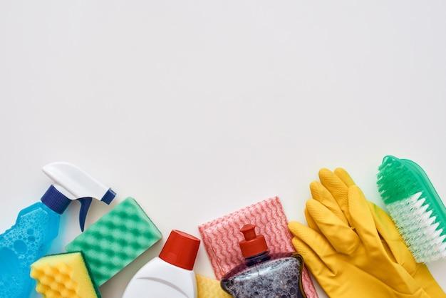 Reinigungswerkzeuge. sprühflasche, orangefarbener reinigungsschwamm und reinigungsmittel einzeln am unteren bildrand. zugeschnittenes foto