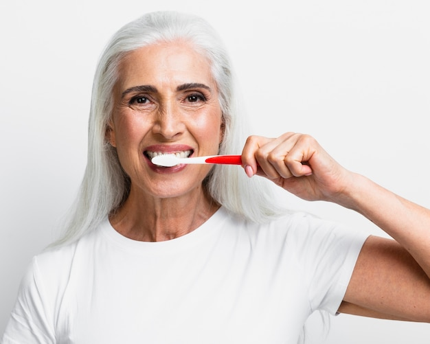 Reinigungszähne der reifen frau mit zahnbürste