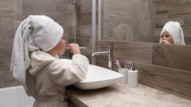 Reinigungszähne des kleinen mädchens im badezimmer gegen spiegel