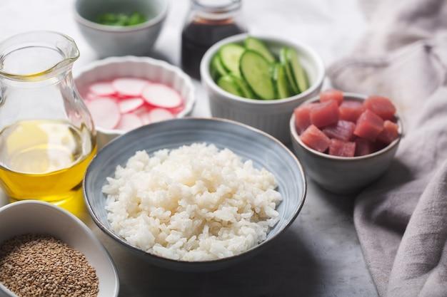 Reis als hauptzutat der traditionellen hawaiianischen poke bowl zubereitet mit thunfisch