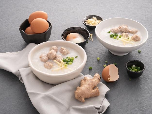Reis congee mit gehacktem schweinefleisch in der weißen schüssel. schüssel reisbrei mit weichem gekochtem ei. asiatisches frühstück