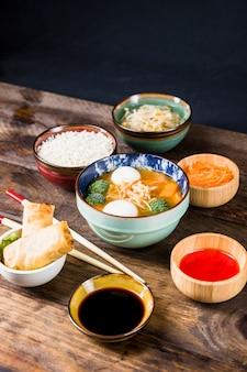 Reis; frühlingsrollen; saucen; bohnen sprießen; geriebene karotten mit fischballsuppe auf schreibtisch vor schwarzem hintergrund