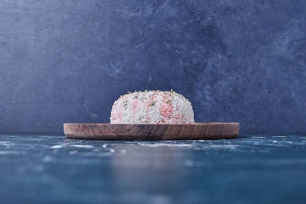 Reis garnieren mit zitrone in einer holzplatte.