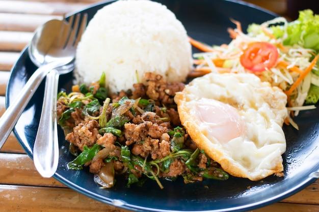 Reis garniert mit gebratenem schweinefleisch und basilikum