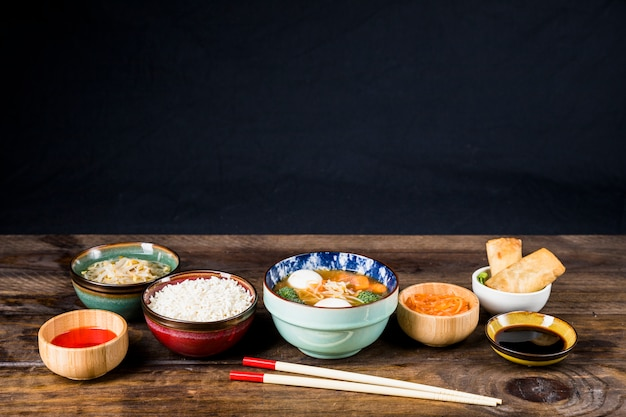 Reis; gekeimte bohnen; frühlingsrollen; fischballsuppe und -soßen mit stäbchen auf tisch vor schwarzem hintergrund
