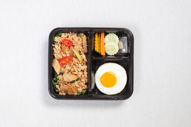 Reis gemischt mit basilikum und schlangenhaut-gourami mit spiegelei in schwarze plastikbox gelegt, auf eine weiße tischdecke gelegt, lebensmittelbox, thailändisches essen.