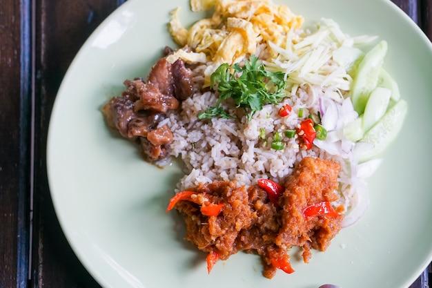 Reis gewürzt mit garnelenpaste und gebratenem fischcurry.