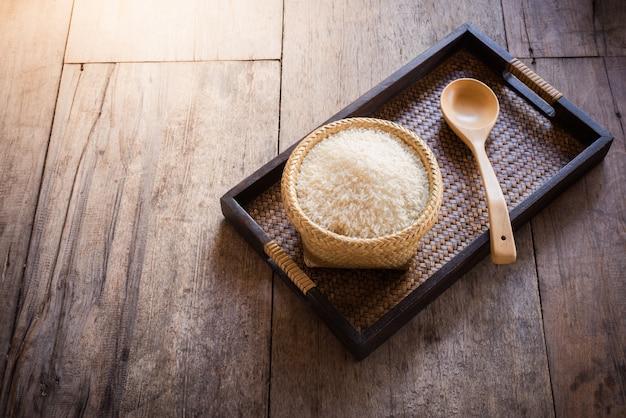 Reis im bambuskorb und im hölzernen löffel auf sacktasche und hölzernem hintergrund