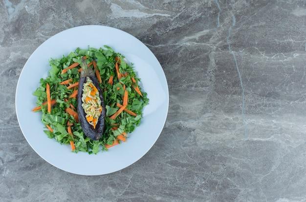 Reis in auberginen auf dem salatteller, auf dem marmortisch.