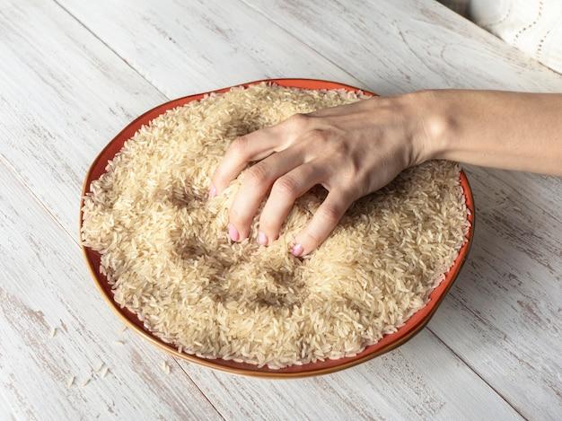 Reis in der hand, die grundlegenden verarbeitungsschritte reis zum essen geeignet. nahansicht.