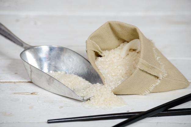 Reis in der kleinen sackzeugtasche auf holztisch