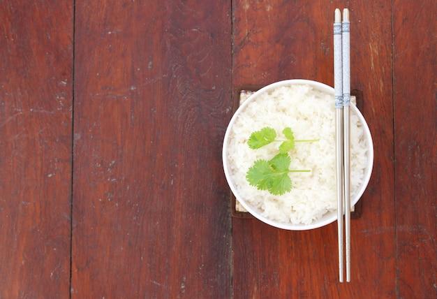 Reis in der weißen schüssel mit essstäbchen