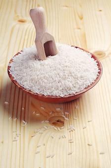 Reis in eine schüssel geben und auf holztisch schaufeln