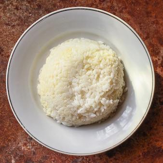 Reis in einem teller garnieren auf dem tisch portionsgröße