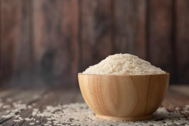 Reis in einer braunen schüssel auf dem holztisch