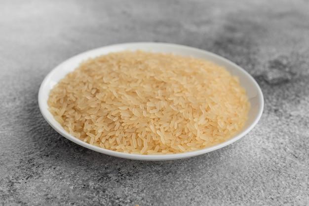 Reis in einer weißen untertasse auf einem grauen konkreten hintergrund