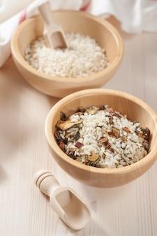 Reis in holzschale mit zutaten für risotto