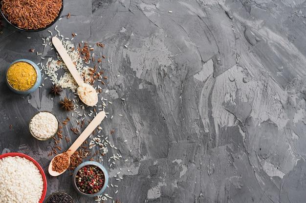 Reis; kurkumapulver; sternanis und pfefferkorn auf schwarzem verwittertem hintergrund mit platz für text