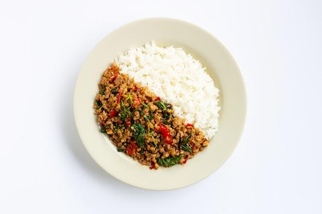 Reis mit angebratenem heißem und würzigem schweinefleisch mit basilikum auf weiß