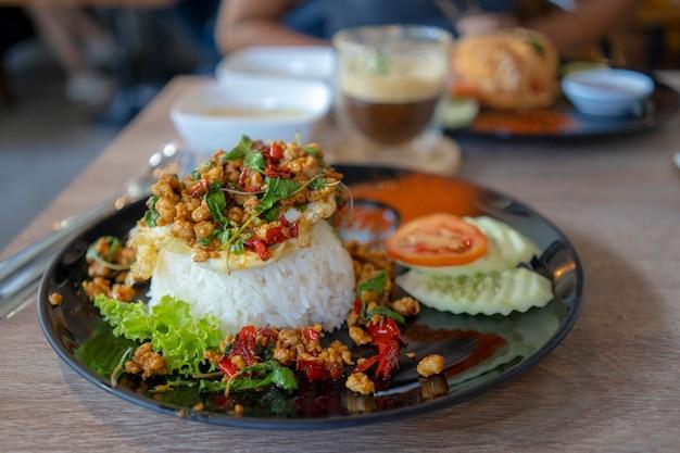 Reis mit basilikum belegt mit spiegeleiern auf dem teller