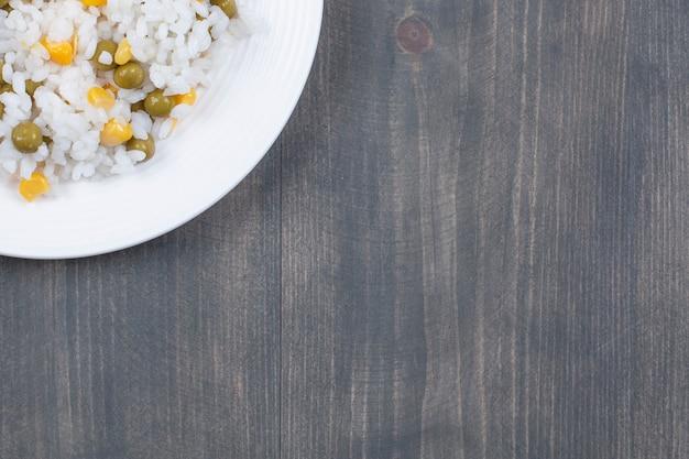 Reis mit dosenmais und erbsen auf weißem teller