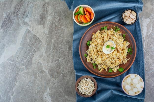 Reis mit ei auf einem teller neben verschiedenen materialien auf einem stoffstück, auf dem marmor.