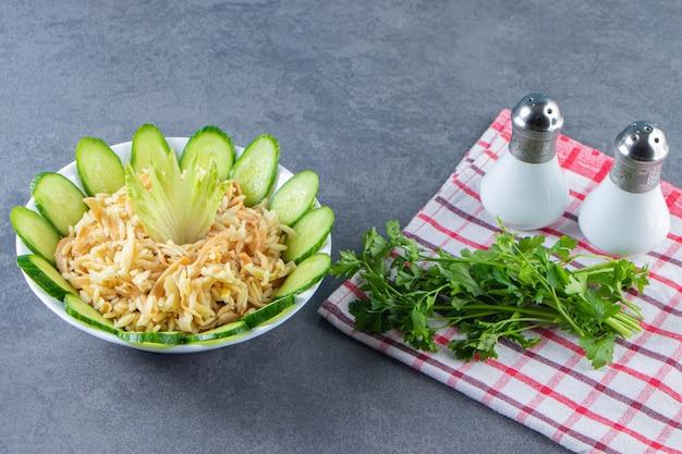 Reis mit fadennudeln und gurken in einer schüssel neben petersilie auf einem handtuch auf der marmoroberfläche.
