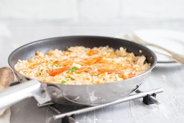 Reis mit fisch und meeresfrüchten in der pfanne auf keramik