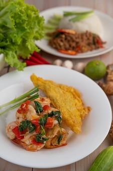 Reis mit garnelen und omelett auf einem weißen teller.