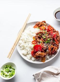 Reis mit gebratenem schweinefleisch, gemüse und frühlingszwiebeln